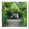 ローズ・ウォークの径の突き当たりに 白い藤棚の下に白いシートに座るご夫婦。