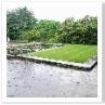 右手の芝が 池を抱え込み、階段脇の花壇は段々に下がる。構成的なデザイン。