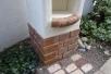 リリーの本体は、耐候性のあるFRP製。ポットなどを飾れる棚も。リアリティのあるレンガと塗りのテクスチャが庭の他のアイテムとの一体感を高めます。