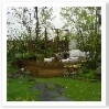 ウッドデッキへ延びる平板の園路。モダンな黒い石が印象を引き締めます。
